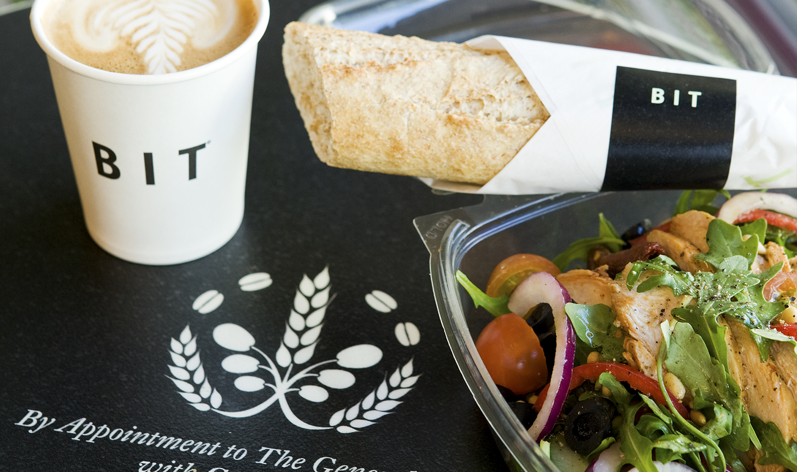 closeup of a wrapped baguette, a tray, and a coffee cup, printed with the BIT logo and symbol