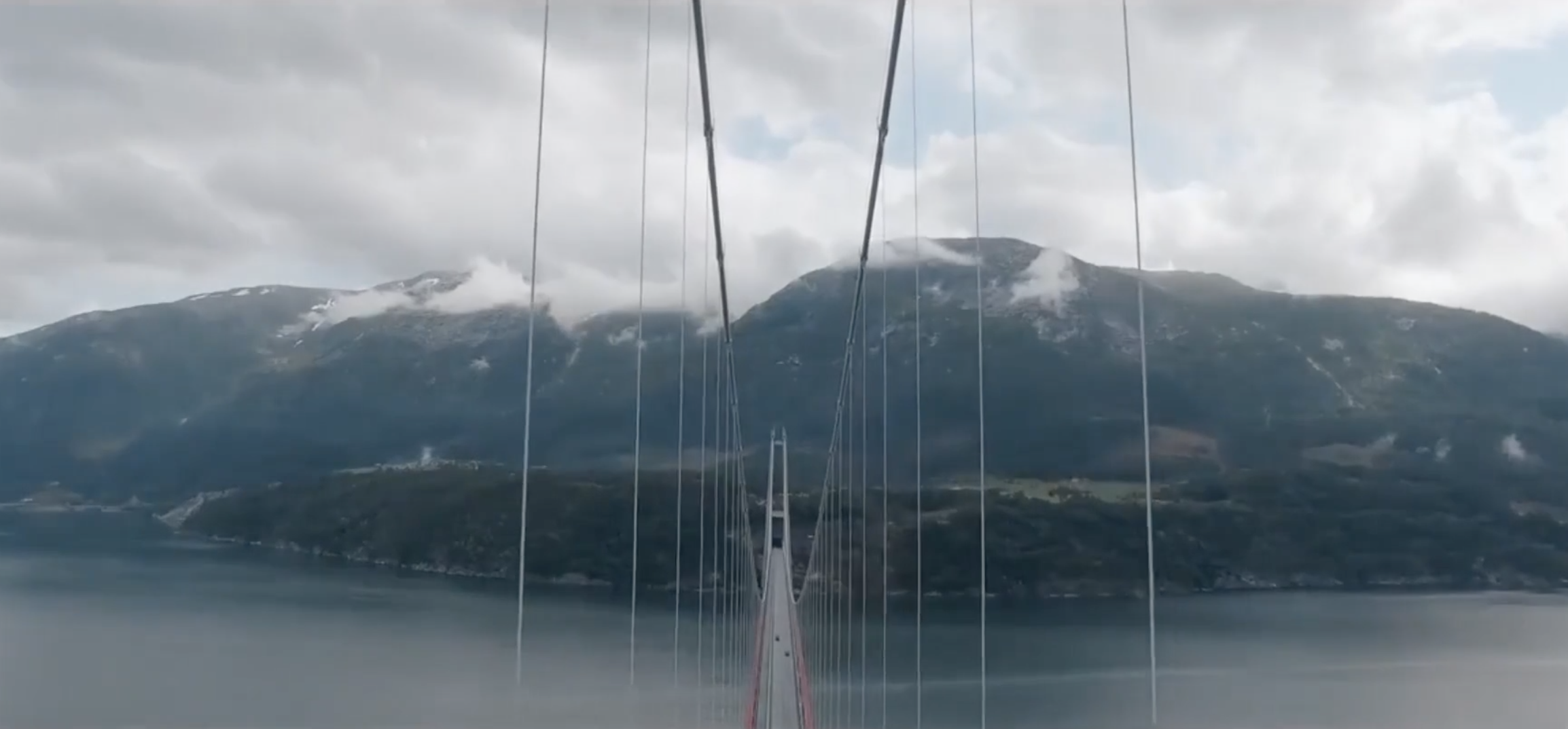 suspension bridge spanning a river/fjord