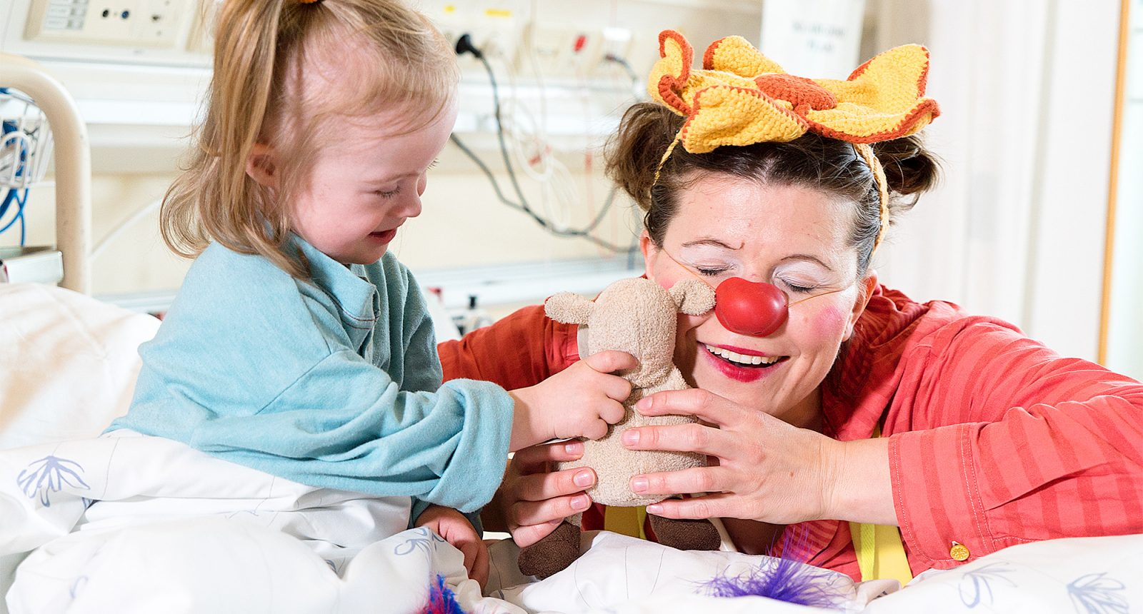 Lady clown playing with a little girl sitting in a hospital bed