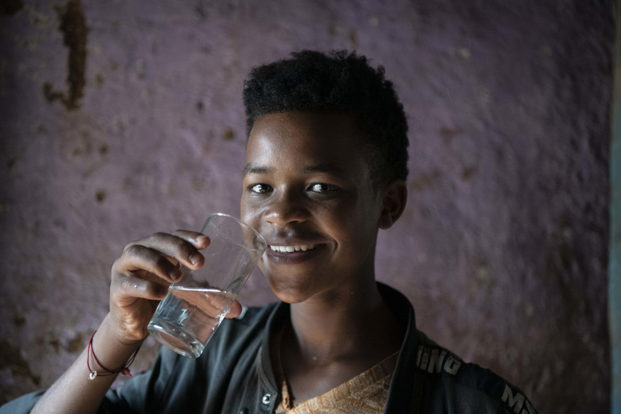 Ung gutt som drikker et glass med rent vann